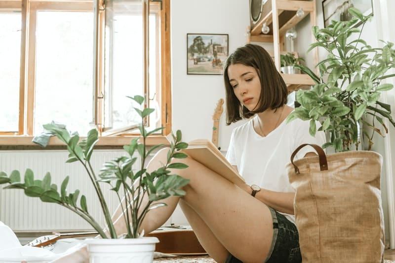 Eine Frau sitzt auf dem Boden und lernt