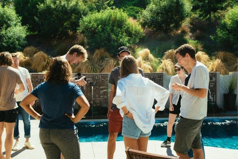 Eine Gruppe junger Leute steht am Pool und hängt ab