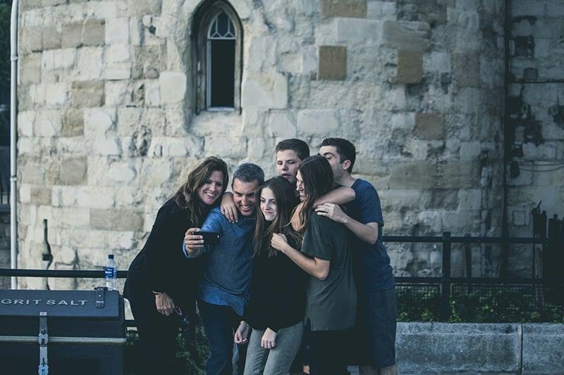 Eine Gruppe von Freunden macht ein Selfie, während sie vor dem Gebäude stehen