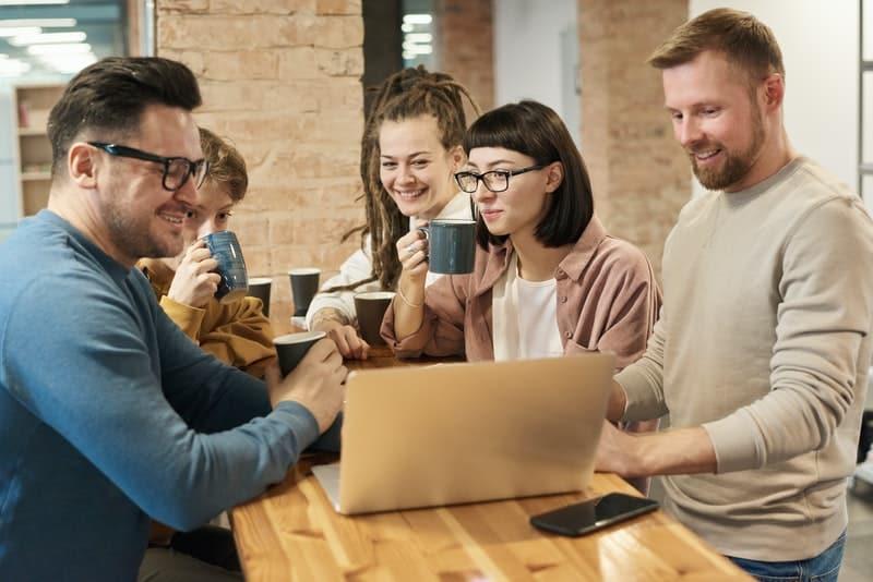 Eine Gruppe von Freunden trinkt Kaffee und schaut sich etwas auf einem Laptop an