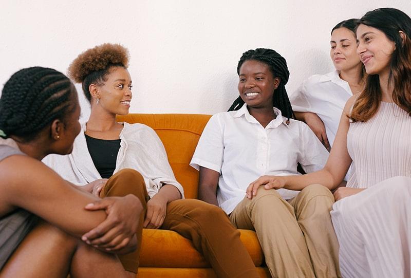 Eine Gruppe von Freundinnen spricht, während sie auf der Couch sitzen
