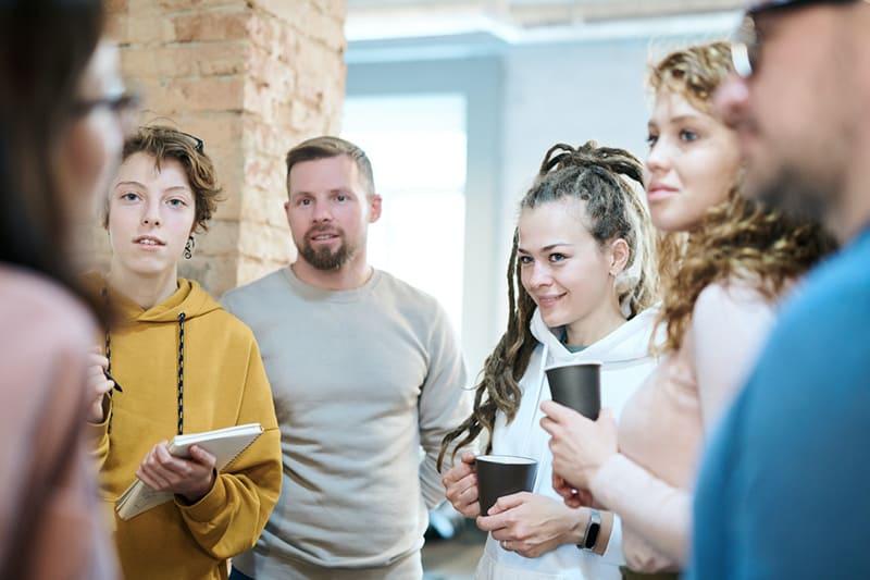Eine Gruppe von Kollegen hört einer Kollegin aufmerksam zu, während sie auf dem Flur steht
