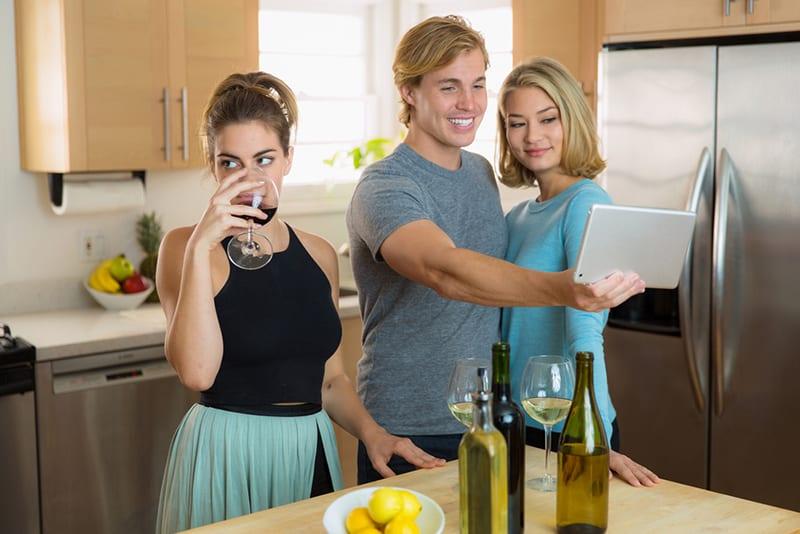 Eine genervte und eifersüchtige Frau, die in der Nähe eines Paares steht und das Selfie auf der Party macht
