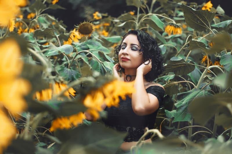 Eine glückliche Brünette steht auf einem Feld von Sonnenblumen