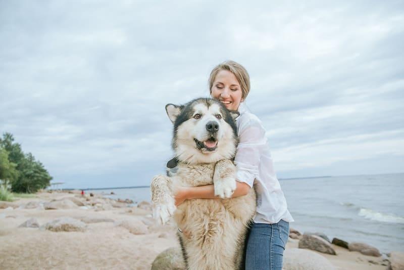 Eine lächelnde Blondine am Strand spielt mit einem Husky