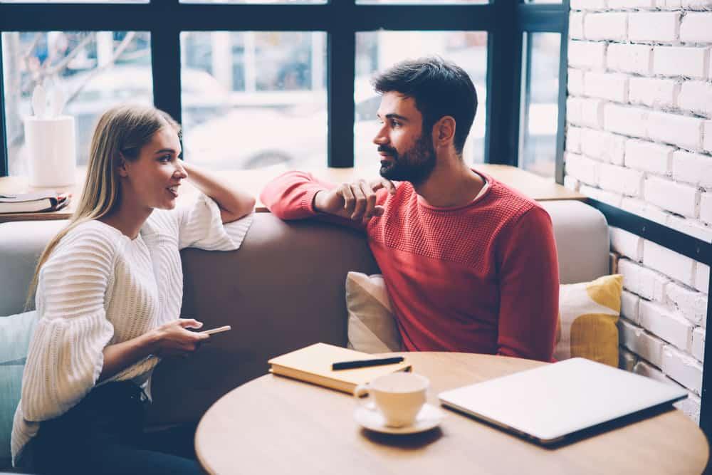 Eine lächelnde Blondine sitzt mit einem Mann mit Bart in einem Café und redet