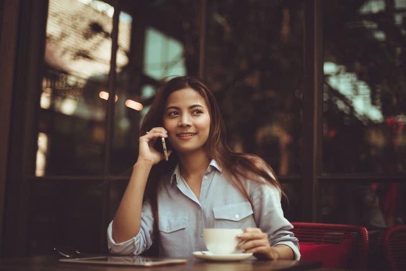 Eine lächelnde Frau in einem Hemd sitzt in einem Café und telefoniert