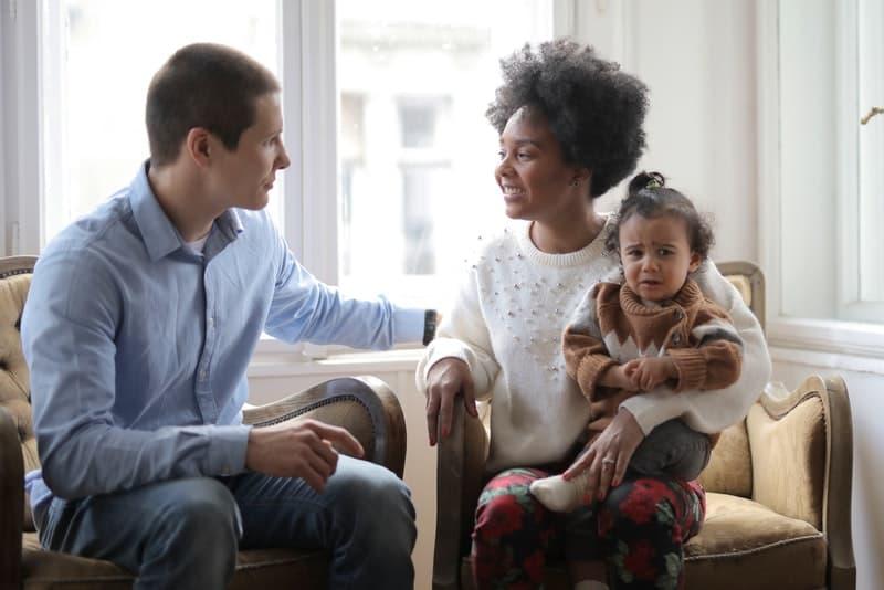 Eine lächelnde Frau mit einem Kind auf dem Schoß spricht mit einem Mann im Haus
