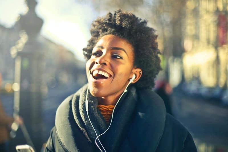 Eine lächelnde schwarze Frau geht die Straße entlang und hört Musik über Kopfhörer