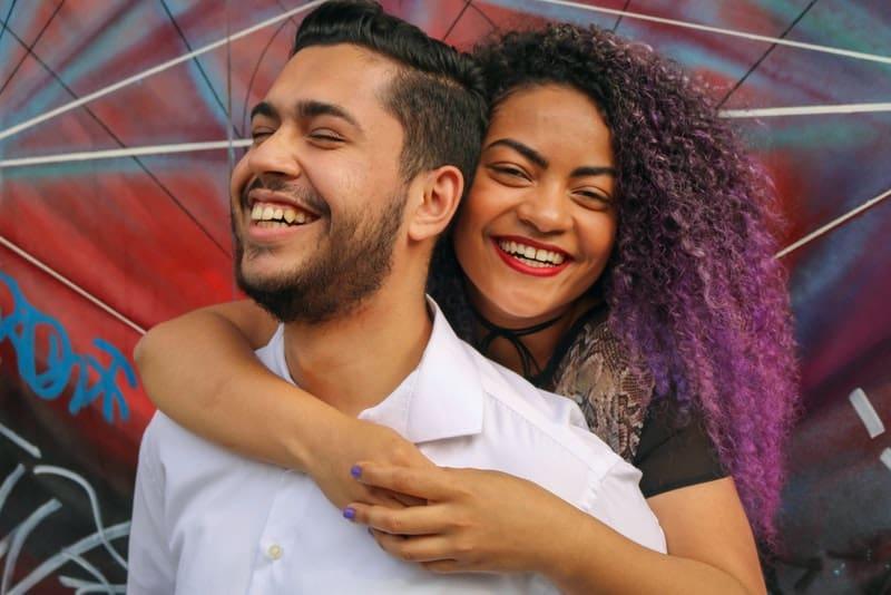 Eine lächelnde schwarze Frau von hinten umarmt ihren Freund