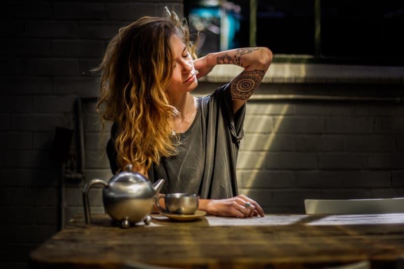 Eine müde Frau sitzt an einem Tisch und hält ihren Hals