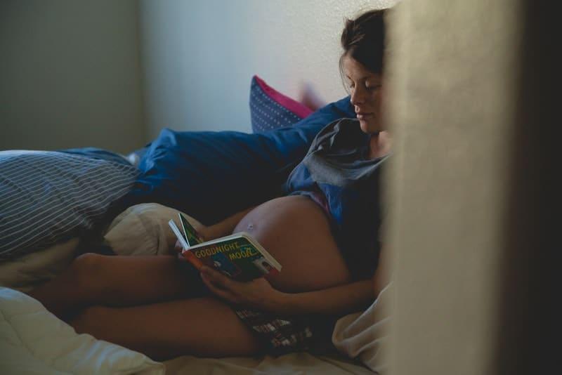 Eine schwangere Frau legt sich hin und liest ein Buch