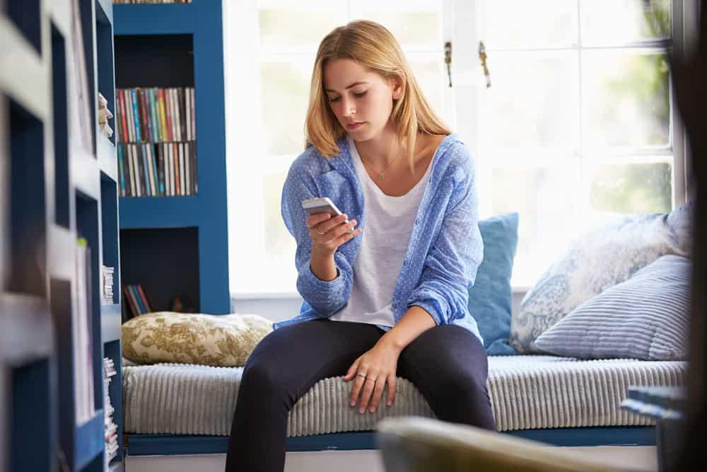 Eine traurige Blondine sitzt mit einem Handy in der Hand auf dem Bett