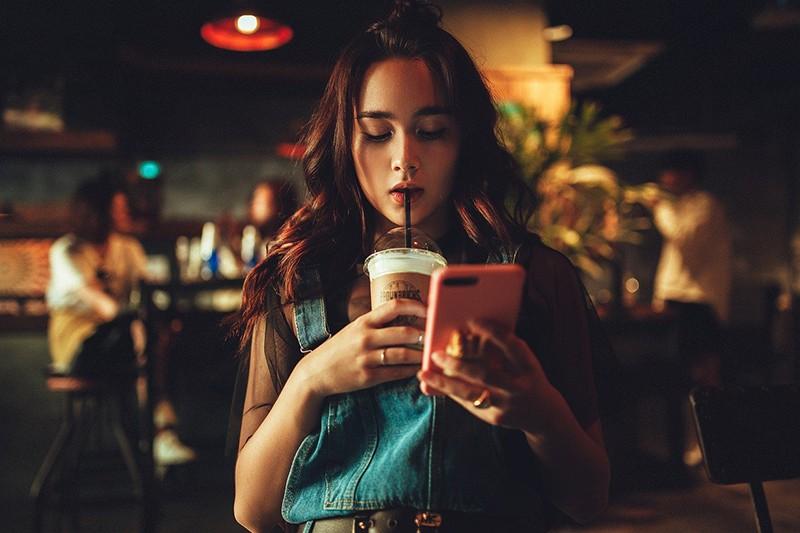 ein Mädchen, das Kaffee trinkt und Smartphone betrachtet