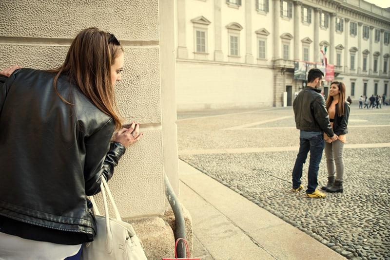 Ex-Freundin spioniert ihren Ex-Freund mit einer anderen Frau aus, während sie sich hinter der Mauer des Gebäudes versteckt