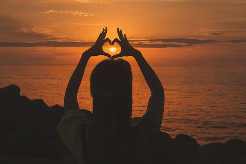 Frau, die bei Sonnenuntergang sitzt und Herz mit den Fingern macht