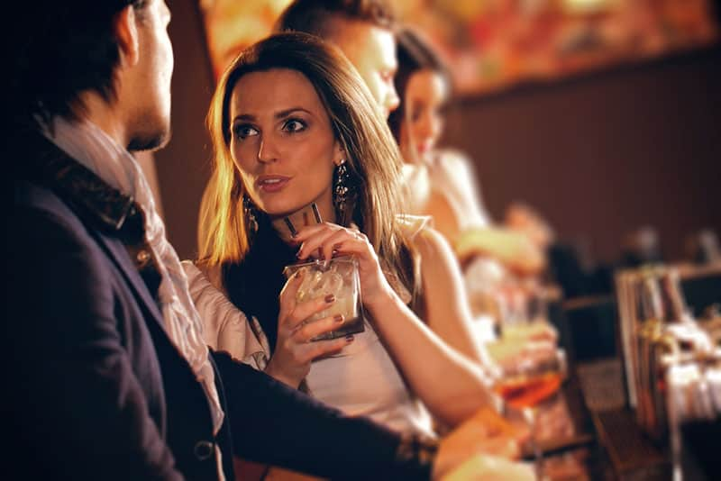 Frau flirtet mit Mann an der Bar