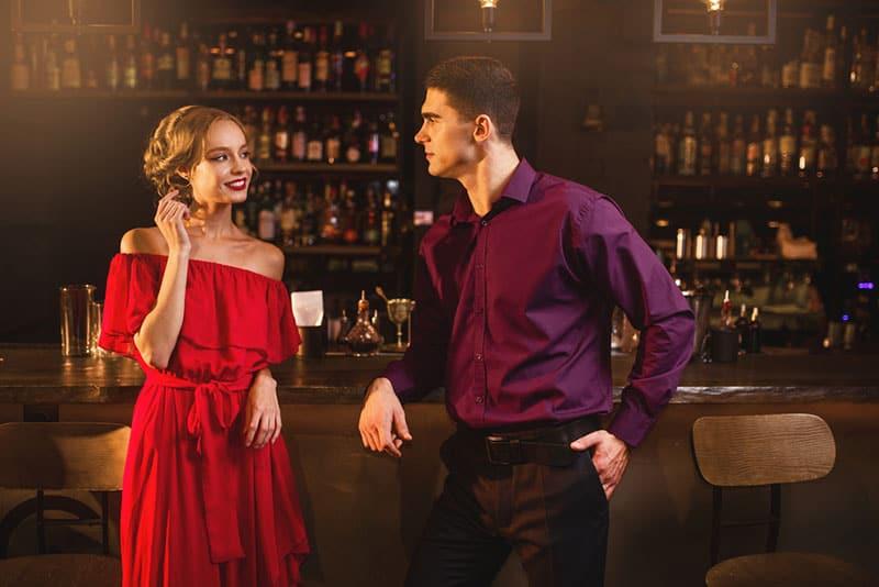 Frau im roten Kleid flirtet mit Mann in der Bar