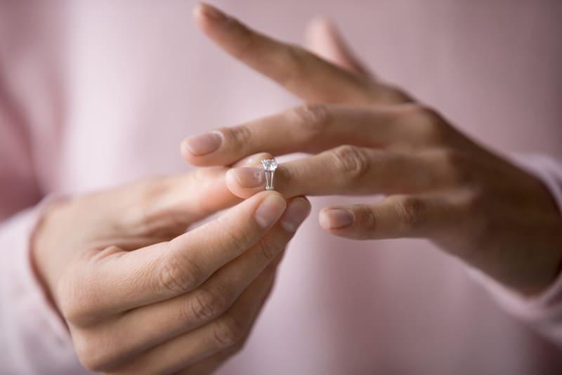 Frau, die Verlobungsring vom Finger nach Trennung abnimmt