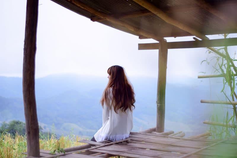 Frau sitzt vor der Hütte