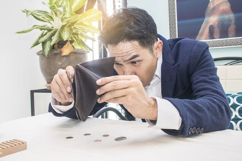Geschäftsmann mit einer leeren Brieftasche, die am Tisch sitzt