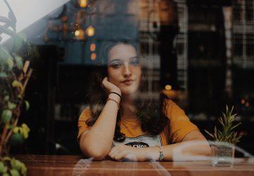 eine Frau, die alleine am Tisch am Fenster sitzt