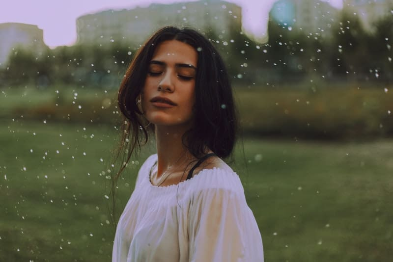 Im Regen steht eine Frau in einem weißen T-Shirt