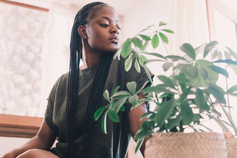 In einem olivgrünen Kleid auf dem Boden sitzt eine traurige nachdenkliche schwarze Frau