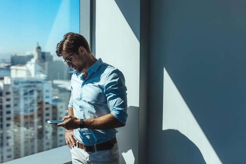 Junger Geschäftsmann, der Handy betrachtet, das neben einem Fenster steht