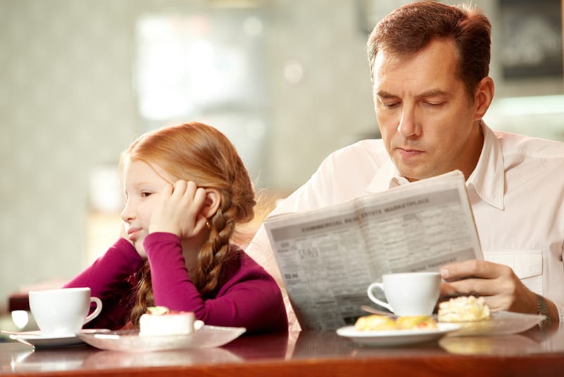 Kleines trauriges Mädchen, das nahe ihrem Vater sitzt, der beim Lesen der Zeitung beschäftigt ist