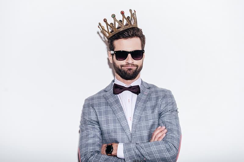 ein Mann, der eine Krone trägt und mit verschränkten Armen steht