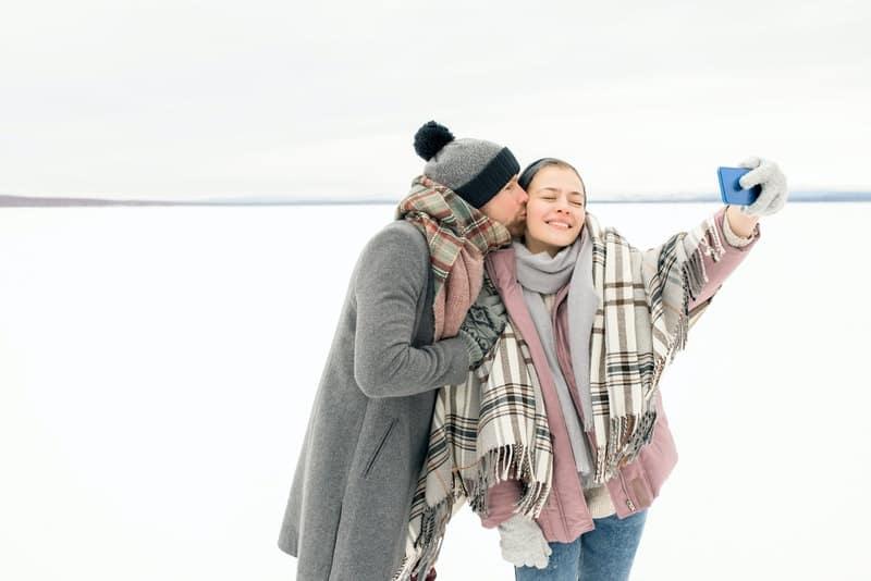 Liebespaar im Schnee, das ein Selfie-Foto macht