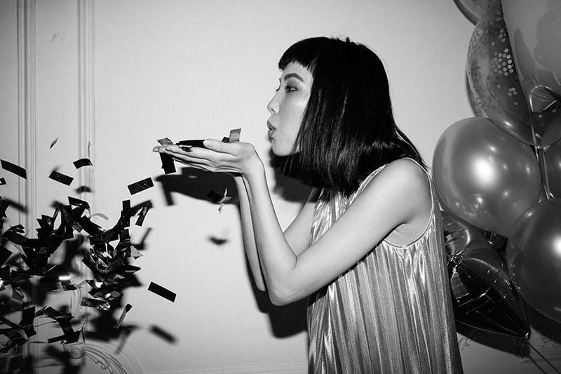 eine Frau, die Konfetti von ihrer Hand auf Geburtstagsfeier bläst