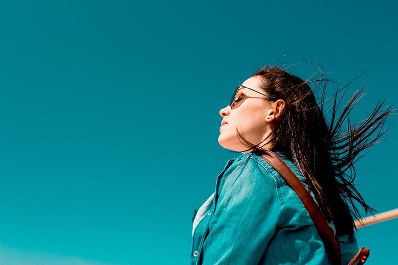 eine Frau, die an einem sonnigen Tag im Wind steht