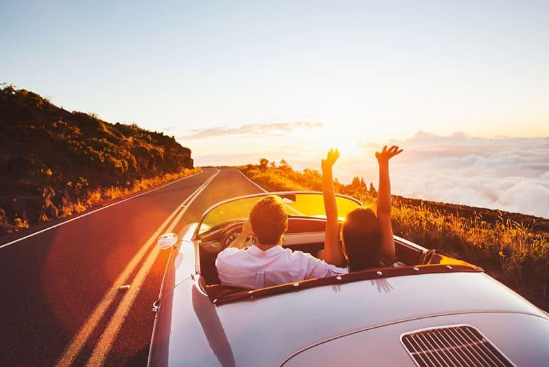 Paar, das bei Sonnenuntergang im Auto fährt
