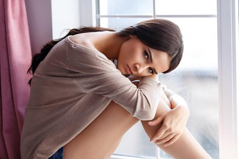 ein ernstes Mädchen, das auf der Fensterbank sitzt und sich auf die Knie stützt
