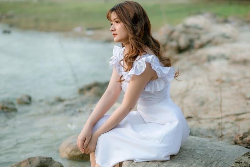 Ein trauriges Mädchen sitzt auf einem Felsen am Fluss