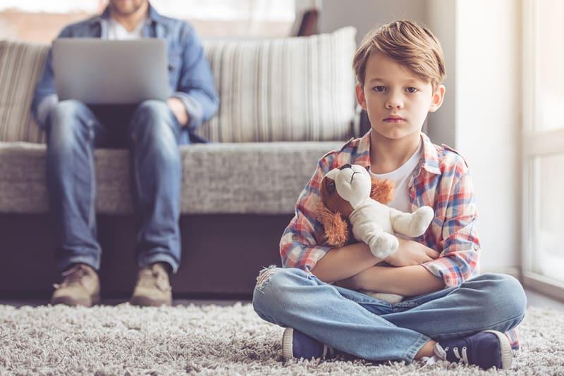 Trauriger kleiner Junge, der ein Spielzeug hält und auf dem Teppich sitzt, während sein Vater hinter ihm auf der Couch arbeitet