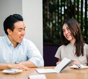 Ein lächelnder Mann und eine lächelnde Frau sprechen, während sie am Tisch sitzen