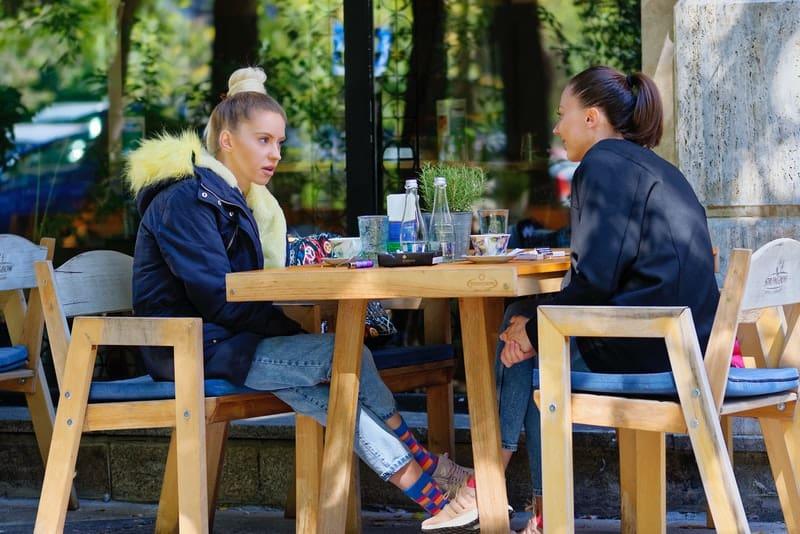 Zwei Freunde sitzen auf der Terrasse eines Cafés und unterhalten sich
