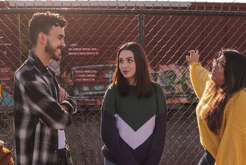 Zwei Mädchen, die einen lächelnden Mann betrachten, während sie mit ihm in der Nähe des Zauns sprechen