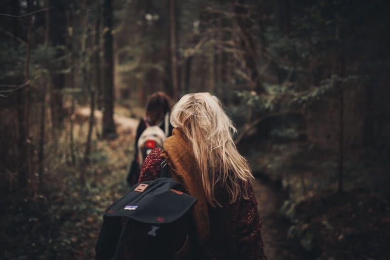 Zwei Mädchen mit Rucksäcken gehen durch den Wald