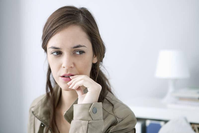 besorgte Frau beißt Nägel
