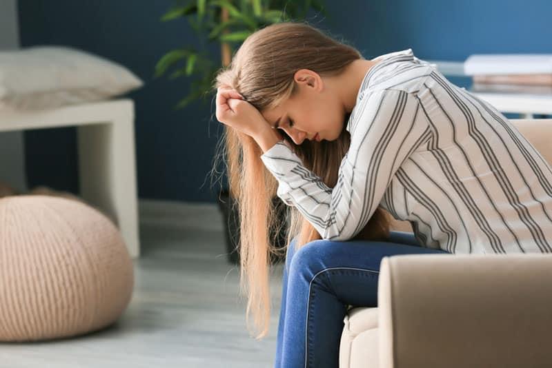 besorgte junge Frau sitzt auf der Couch