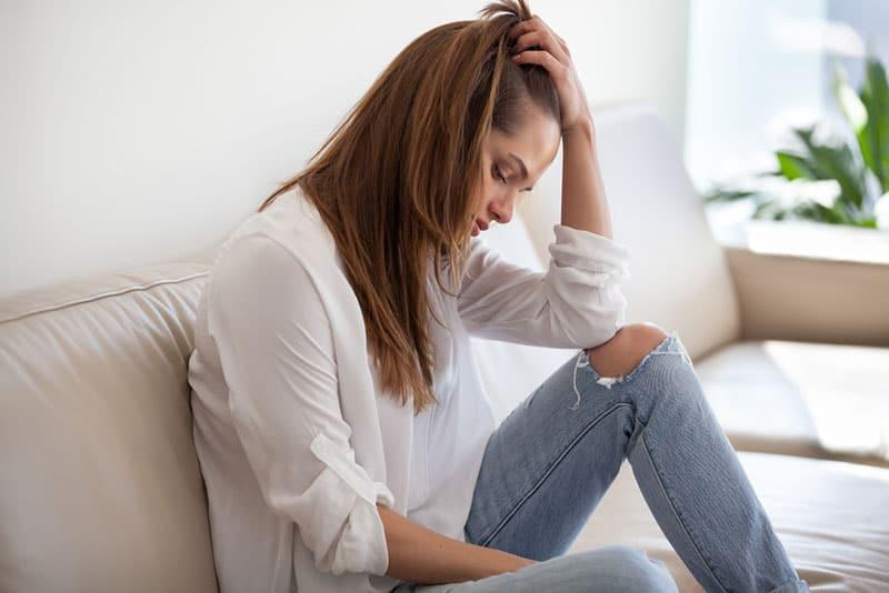 besorgte nachdenkliche Frau, die auf der Couch sitzt