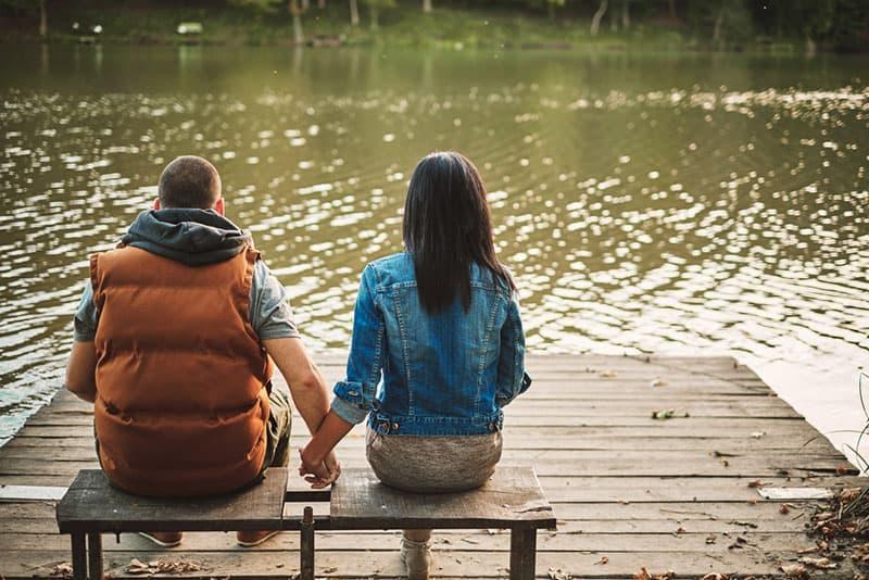 das Paar Händchen haltend und am See sitzend