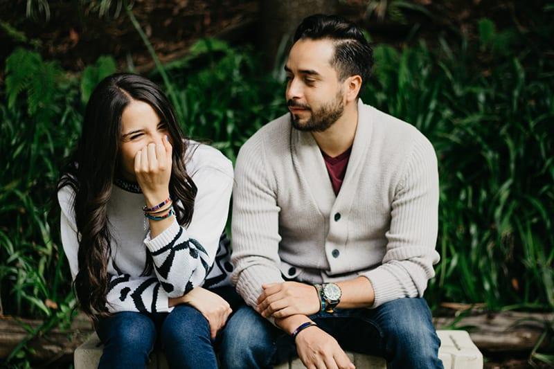 Die lachende Frau saß neben einem Mann, der sie ansah