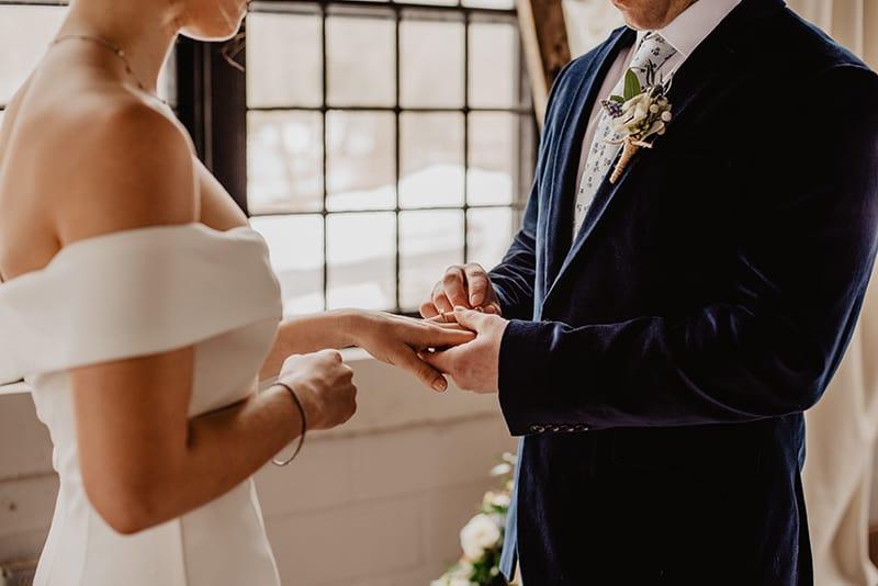 ein Bräutigam, der während der Hochzeitszeremonie einen Ring auf den Finger der Braut legt