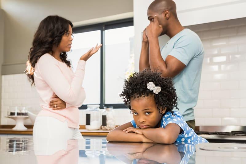 ein Ehepaar, das in der Küche vor ihrer Tochter streitet