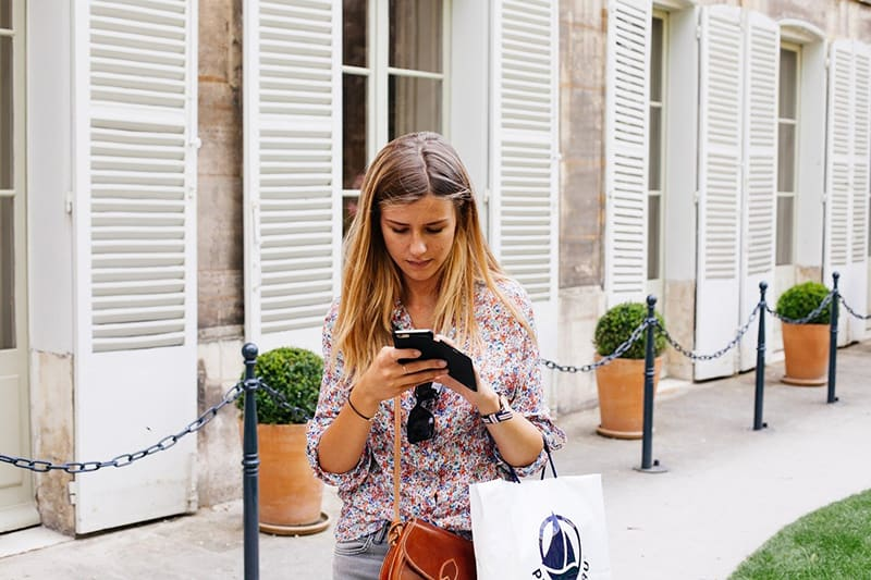 ein Mädchen, das mit einem Smartphone hält und eine Tragetasche hält, während es vor dem Gebäude steht